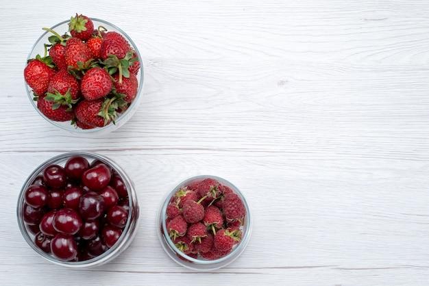 Vista de cima cerejas vermelhas ácidas frescas inteiras e maduras com morangos e framboesas na mesa clara fruta cor fresca azeda doce suculenta