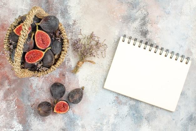 Vista de cima cesta de figos flores secas de figos em um bloco de notas em fundo cinza