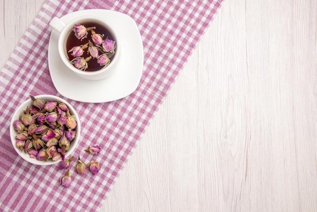 Vista de cima chá de ervas uma xícara de chá de ervas no pires ao lado da tigela de ervas na toalha de mesa quadriculada sobre a mesa