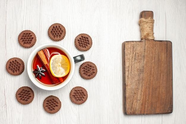 Vista de cima, chá de limão e canela arredondado com biscoitos e uma tábua de cortar na mesa de madeira branca