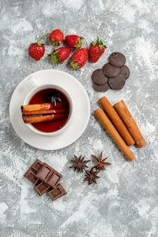 Vista de cima, chá de sementes de anis de canela e alguns chocolates de morangos sementes de anis de canela no lado esquerdo da mesa