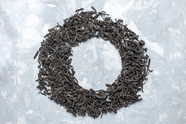 Vista de cima chá seco de cor preta formando um círculo na mesa de luz, chá de grãos de cor seca