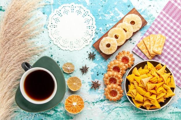 Vista de cima, chips picantes com biscoitos, anéis de abacaxi seco com chá e biscoitos na superfície azul chips cor do lanche caloria crocante