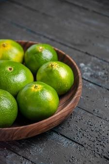 Vista de cima, close-up, limas na mesa, limas verde-amarelas em uma tigela na mesa cinza