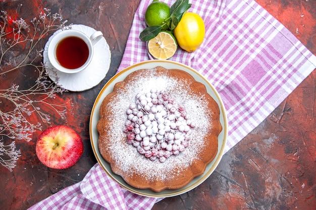 Vista de cima, close-up, um bolo, um bolo com frutas, maçã, uma xícara de chá, frutas cítricas, na toalha de mesa