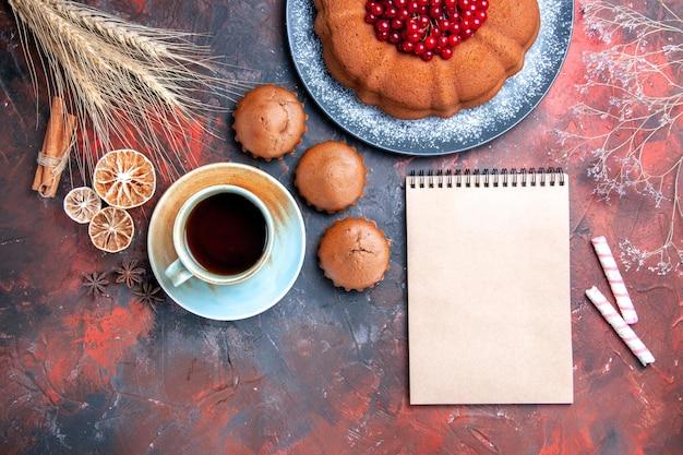 Vista de cima, close-up, uma xícara de chá, um bolo, bolinhos, uma xícara de chá, doces, canela, paus, caderno, branco