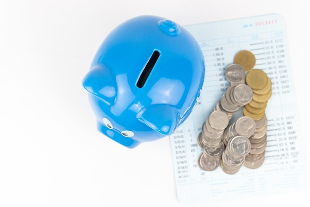 Vista de cima cofrinho azul com pilha de moedas no fundo branco do livro de contas
