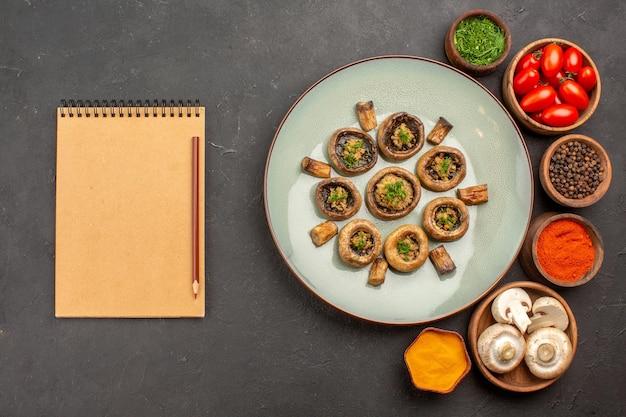 Vista de cima cogumelos cozidos com tomates e temperos em um prato escuro de mesa fazendo um jantar de cogumelos