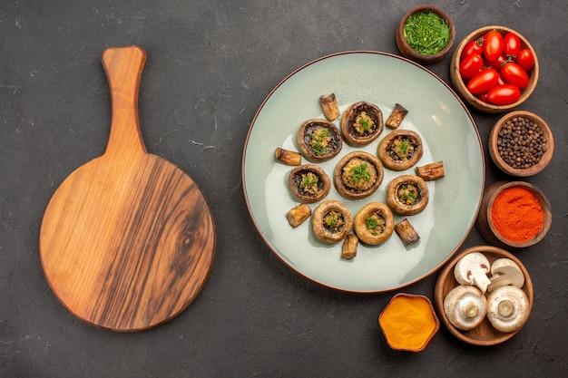 Vista de cima cogumelos cozidos com tomates e temperos na superfície escura prato refeição cozinhando cogumelo jantar
