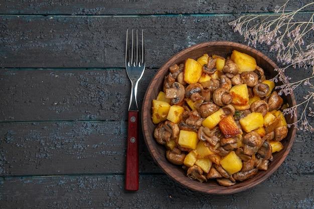 Vista de cima cogumelos e batatas, batatas com cogumelos em uma tigela entre um garfo e galhos de árvores