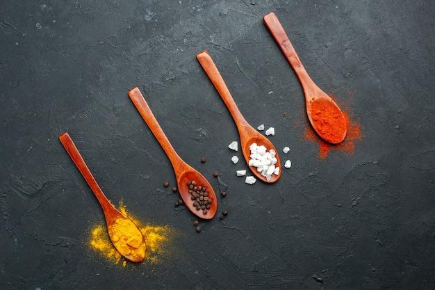 Vista de cima, colheres de pau na linha diagonal com cúrcuma pimenta preta sal pimenta vermelha em pó na mesa