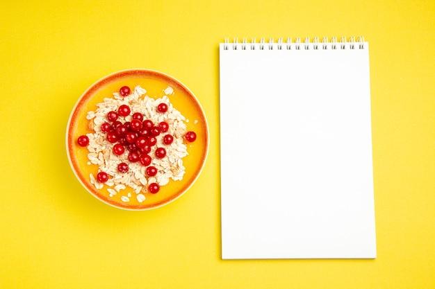 Vista de cima com bagas vermelhas, aveia e frutas vermelhas no caderno branco com laranja