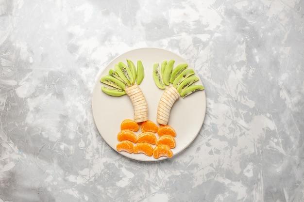 Vista de cima com frutas fatiadas, kiwis, bananas e tangerinas em uma mesa de frutas brancas claras exóticas tropicais frescas maduras