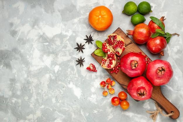Vista de cima com romãs vermelhas frescas com tangerinas e ameixas na mesa branca