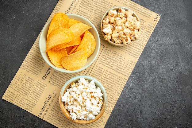 Vista de cima com saborosos chips de queijo com diferentes lanches para a hora do filme no fundo escuro