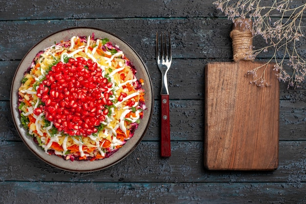 Vista de cima comida de natal saborosa prato de natal com sementes de romã ao lado do garfo e tábua de cortar na mesa cinza
