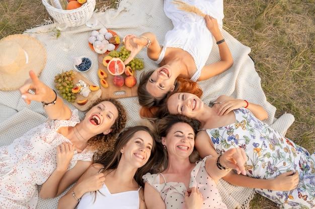 Vista de cima. companhia de namoradas bonitas se divertir e desfrutar de um piquenique ao ar livre.