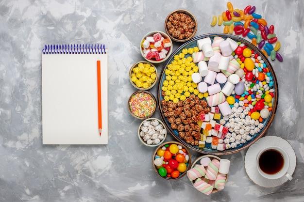 Vista de cima, composição de doces, doces de cores diferentes com bloco de notas de marshmallow e chá na mesa branca.
