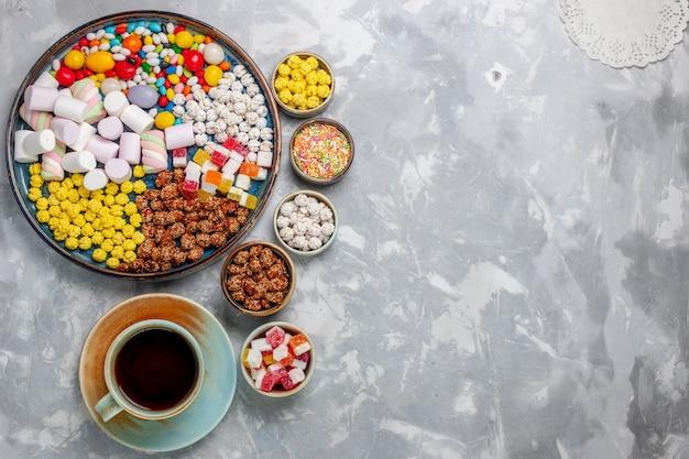 Vista de cima, composição de doces, doces de cores diferentes com marshmallow e xícara de chá na mesa branca.