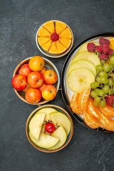 Vista de cima, composição de frutas diferentes, frutas frescas e fatiadas em fundo escuro frutas frescas maduras saúde madura