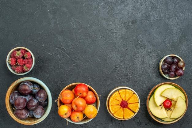 Vista de cima, composição de frutas diferentes, frutas frescas e fatiadas em fundo escuro frutas maduras saúde maduras frescas