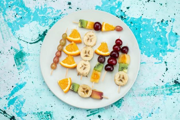 Vista de cima composição de frutas fatiadas em palitos dentro de um prato branco na mesa brilhante frutas exóticas biscoitos açúcar