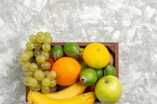 Vista de cima composição de frutas frescas bananas uvas e feijoa no fundo branco fruta suave vitamina saúde fresca