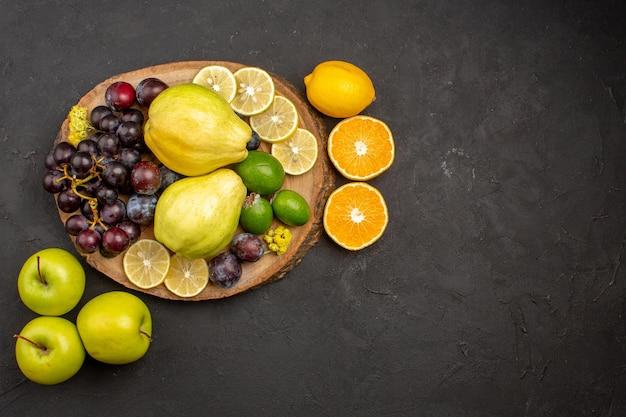 Vista de cima composição de frutas frescas frutas maduras e maduras em frutas de chão escuro vitaminas maduras frescas e maduras