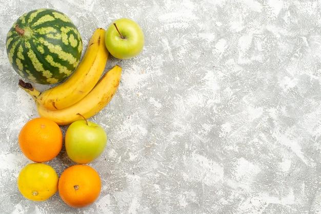 Vista de cima composição de frutas frescas maçãs melancia e bananas no fundo branco frutas frescas maduras vitamina de cor