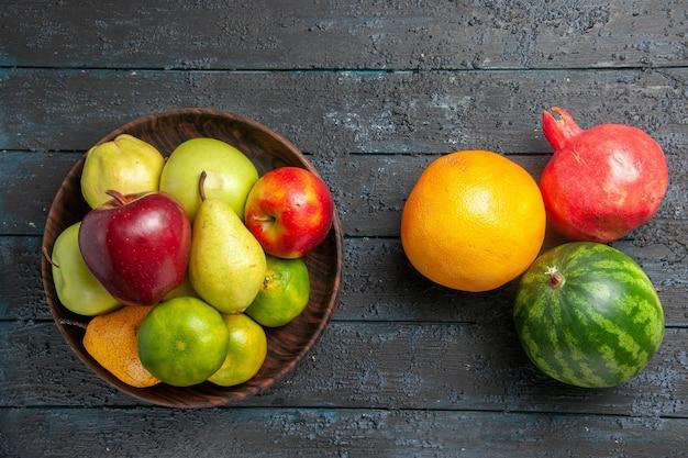 Vista de cima composição de frutas frescas maçãs, peras e tangerinas em azul-escuro mesa fruta madura cor da árvore fresca suave