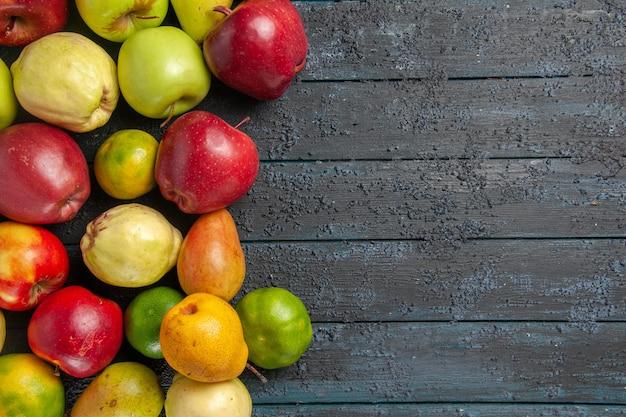 Vista de cima composição de frutas frescas maçãs, pêras e tangerinas na mesa azul-escuro frutas maduras cor da árvore suave, muitas frescas
