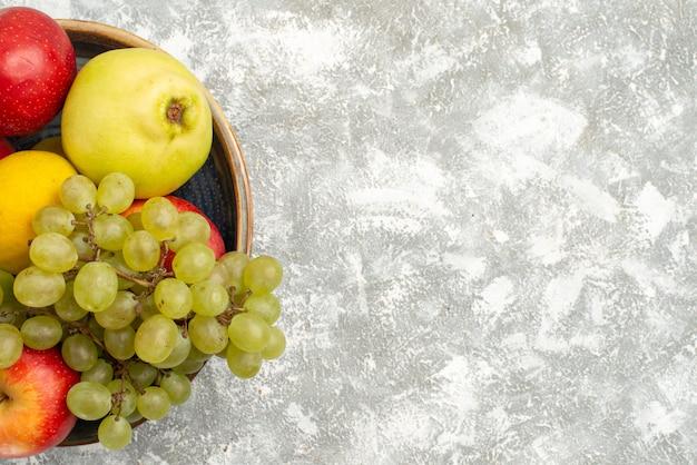 Vista de cima composição de frutas frescas maçãs uvas e outras frutas no fundo branco frutas frescas maduras cor madura