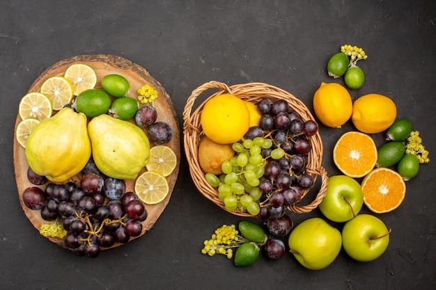 Vista de cima composição de frutas frescas maduras fatiadas e frutas maduras na superfície escura frutas frescas vitaminas maduras maduras