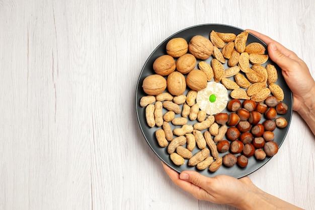 Vista de cima, composição de nozes diferentes, avelãs frescas, nozes e amendoins dentro do prato branco, porca de mesa, lanche, muitas plantas