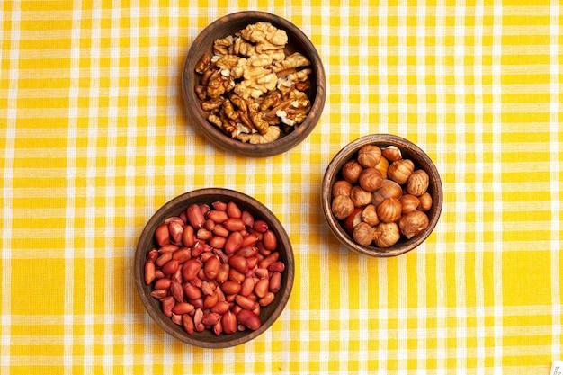 Vista de cima composição de nozes nozes frescas descascadas, amendoim e avelãs no branco, porca de mesa, muitas árvores, planta casca lanche