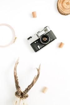 Vista de cima, conceito de fotógrafo moderno plana leigos. câmera retro, chifres de cabra e xícara de café da manhã em branco.