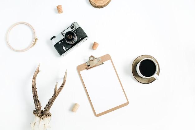 Vista de cima, conceito de fotógrafo moderno plana leigos. câmera retro, chifres de cabra, prancheta e xícara de café da manhã em branco