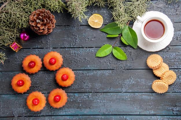 Vista de cima cone arredondado de cupcakes de cereja abeto folhas brinquedos de natal fatia de limão uma xícara de chá e biscoitos na mesa de madeira escura com espaço de cópia