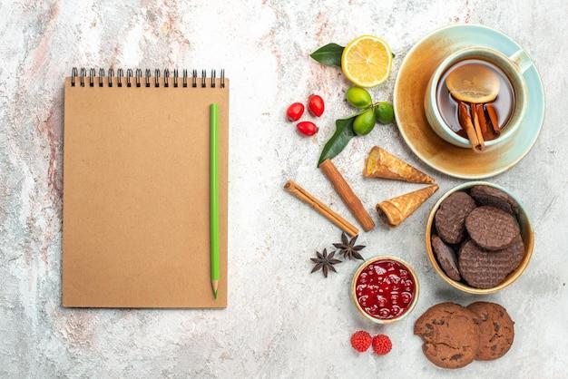 Vista de cima cookies, uma xícara de chá preto com limão, canela, limão, geléia, caderno, anis estrelado e lápis
