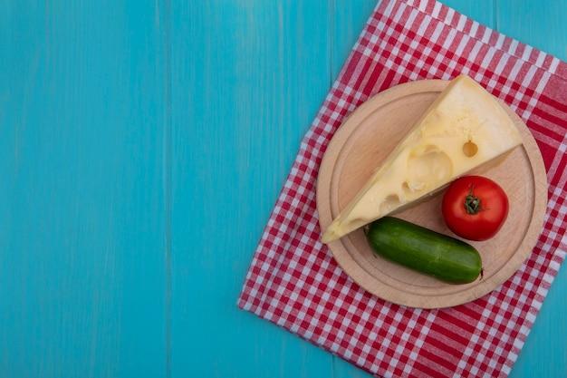 Vista de cima cópia espaço queijos maasdam com pepino e tomate em um carrinho sobre uma toalha vermelha quadriculada em um fundo turquesa