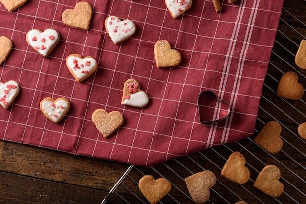 Vista de cima, corações de biscoitos caseiros com cobertura branca de cobertura e cobertura de massa em toalha de cozinha marrom e grelha de metal para o dia dos namorados