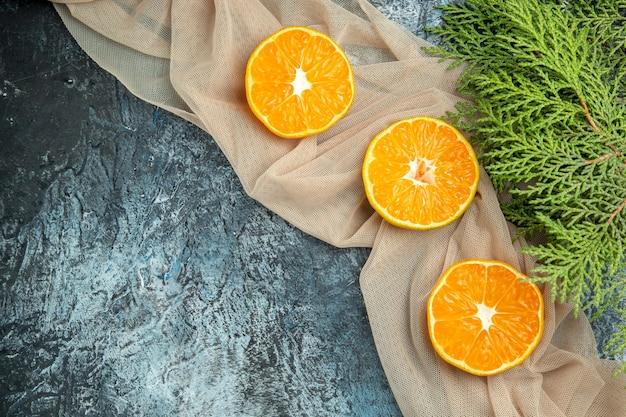 Vista de cima, corte laranjas em galhos de pinheiro xale bege em espaço livre de superfície escura