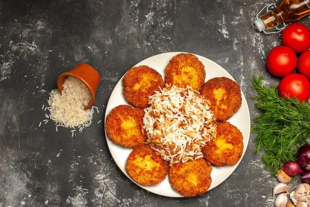 Vista de cima costeletas fritas com arroz cozido e verduras em um prato de mesa cinza