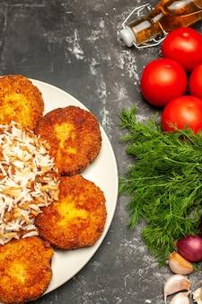 Vista de cima costeletas fritas com arroz cozido e verduras na superfície cinza prato foto de carne