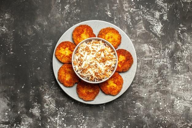 Vista de cima costeletas fritas com arroz cozido em rissole de carne de mesa escura
