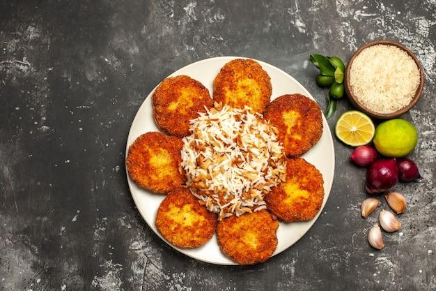 Vista de cima costeletas fritas com arroz cozido em rissole de carne de prato escuro de mesa