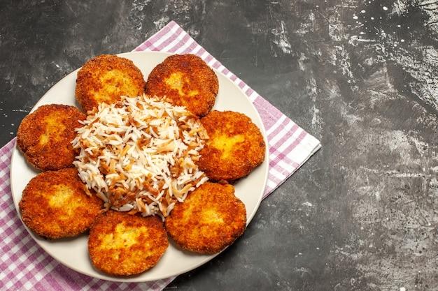 Vista de cima costeletas fritas com arroz cozido em rissole de prato de carne escura de mesa