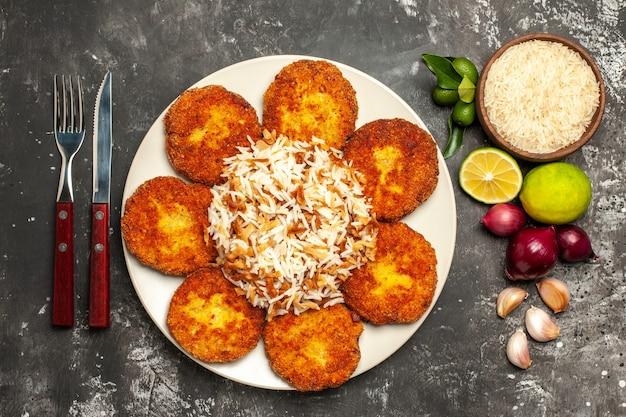 Vista de cima costeletas fritas com arroz cozido em um prato de comida de superfície escura rissole de carne