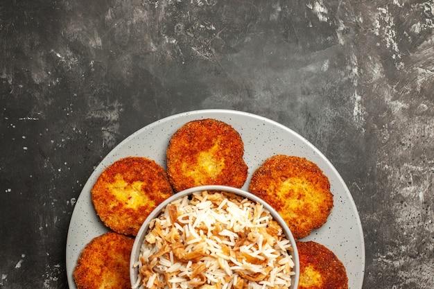 Vista de cima costeletas fritas com arroz cozido em um prato de superfície escura com carne rissole