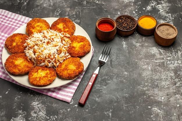 Vista de cima, costeletas fritas saborosas com arroz e temperos em uma refeição de rissole de carne de superfície escura